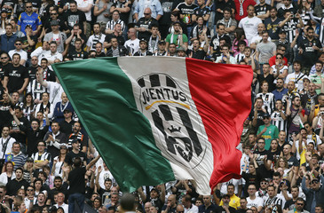 Juventus' supporters wave a giant Italian flag with the club's logo during their Italian Serie A soccer match against Palermo at the Juventus stadium in Turin