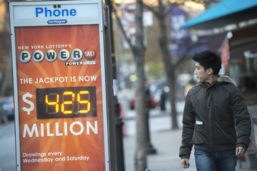 Man walks near a sign advertising the Powerball lottery in New York