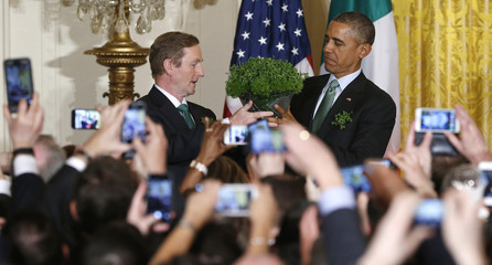 Ireland's PM Kenny presents a bowl of shamrocks to Obama at a St. Patrick's Day reception in the East Room of the White House in Washington