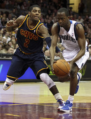 Cleveland Cavaliers' Irving reaches in for the ball against Dallas Mavericks' Beaubois as he drives to the basket during the fourth quarter of their NBA basketball game in Cleveland