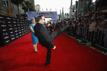 "Cast member Ricky Gervais kicks into the air as his partner Jane Fallon stands nearby at the premiere of ""Muppets Most Wanted"" at El Capitan theatre in Hollywood"