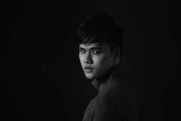 Young asian man's portrait against black background
