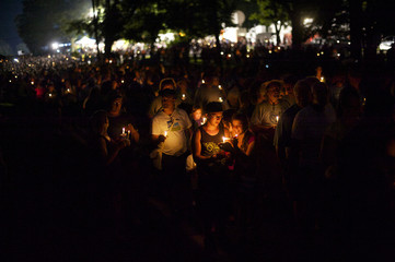 Visitors carry candles into the Soldiers' National Cemetery for the Memorial Luminaria during events marking the 150th anniversary of the Battle of Gettysburg, in Gettysburg, Pennsylvania