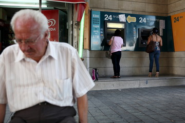 People withdraw money from automated teller machines in Nicosia, Cyprus