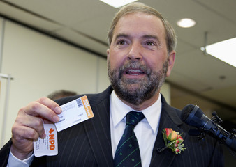 NDP member of parliament Mulcair holds party membership cards as announces his intention to run for party's leadership in Montreal