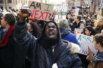 People shout slogans against police as they take part in a march against police violence, in New York