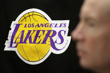 The Los Angeles Lakers logo is pictured past the profile of Lakers spokesman John Black during a news briefing regarding the death of longtime Lakers owner Jerry Buss, at the Lakers' practice facility in El Segundo