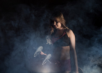 Fitness young woman in training with dumbbells, sporty muscular female brunette in smoke