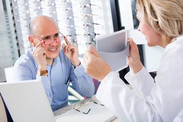 Adult consultant and male choosing glasses