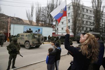 A woman waves a Russian flag as armed servicemen wait near Russian army vehicles outside a Ukrainian border guard post in the Crimean town of Balaclava