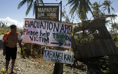 A sign asking for aid is posted by typhoon Bopha victims along a road in Maparat town
