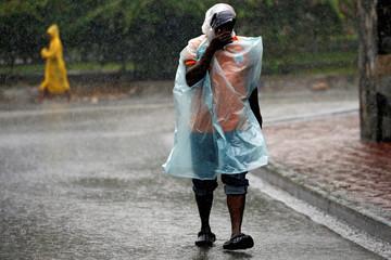 People walk down the street while Hurricane Matthew passes Port-au-Prince