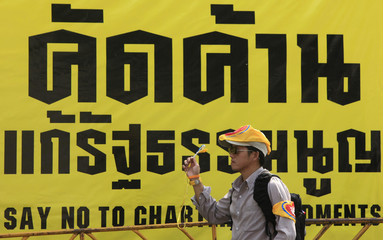 A yellow shirt supporter of PAD uses a noise maker during a rally outside the Parliament in Bangkok