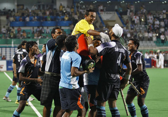 India's players carry goalkeeper Bharat Kumar Chetri as they celebrate winning a penalty shootout against England in their men's field hockey semi-final match at the Commonwealth Games in New Delhi