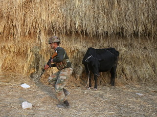 An Indian army soldier moves past a cow during a patrol outside the Indian Air Force base at Pathankot in Punjab