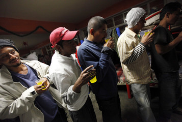 """Central American migrants stand in line as they wait for Christmas dinner at """"La Lecheria"""" in Tultitlan"""