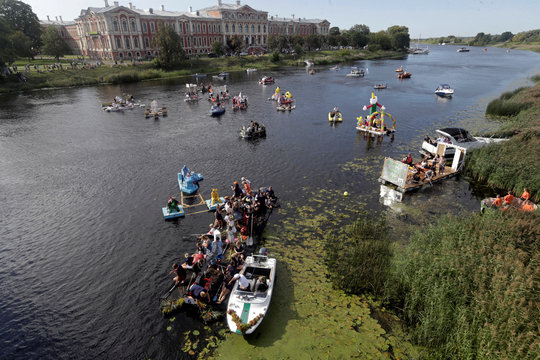 People rest on their home-made boats after finishing the Milk Carton Boat Race in Jelgava