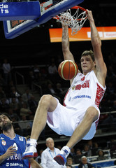 Mozgov of Russia hangs on the rim after a slam dunk against Serbia during their FIBA EuroBasket 2011 quarter-final basketball game in Kaunas
