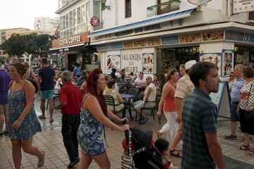 Tourists walk along San Miguel street in downtown Torremolinos