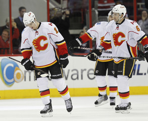 Calgary Flames' Backund and Sarich react during their loss to the Carolina Hurricanes in their NHL hockey game in Raleigh