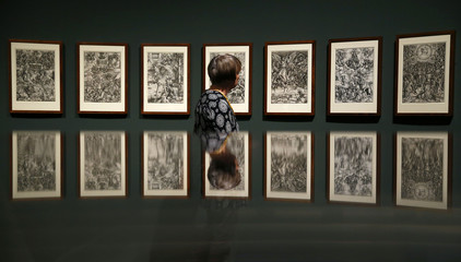 A woman looks at pictures called 'The Apocalypse' by German Renaissance painter Duerer during preview of 'Duerer' exhibition at Staedel museum in Frankfurt