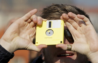 A man watches a partial solar eclipse looking through a floppy disc from the medieval Charles Bridge in Prague