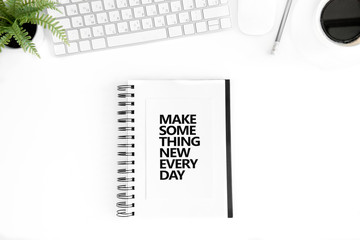 top view of make something new every day motivational quote in diary, computer mouse and keyboard isolated on white