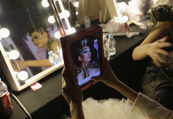 A model uses an iPad to take a photo of herself backstage before the MGPIN collection show by Maogeping Image Design Art School at China Fashion Week in Beijing