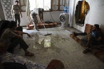 A Free Syrian Army fighter cleans the floor as fellow fighters rest inside a room in Deir al-Zor