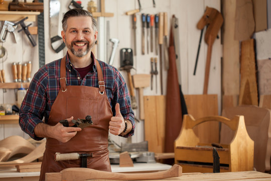 Happy Carpenter/Middle ages handsome carpenter finished creating cabriolet legs and smiles to the camera