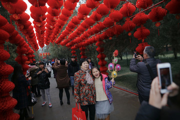 People have their pictures taken under red lanterns at the temple fair at Ditan Park in Beijing
