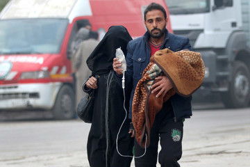 A man carries a child with an IV drip as he flees deeper into the remaining rebel-held areas of Aleppo