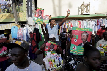 Supporters of presidential candidate Moise Jean Charles of Pitit Desalin political platform hold posters during a rally in Port-au-Prince