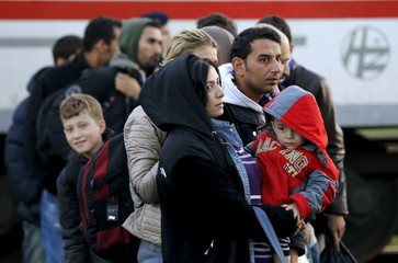 Migrants wait to board to a bus after exiting a train at a train station in Croatia's Cakovec