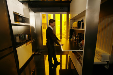 Hong Kong architect Gary Chang slides away a track-mounted metal wall that bears a plasma TV to reveal a kitchen in his 32-square-metre apartment in Hong Kong