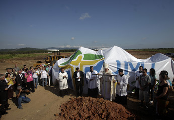 Rio de Janeiro's Archbishop Dom Orani Tempesta places a cross during a blessing ceremony to mark the beginning of works at the farm Vila Mar site in Rio de Janeiro