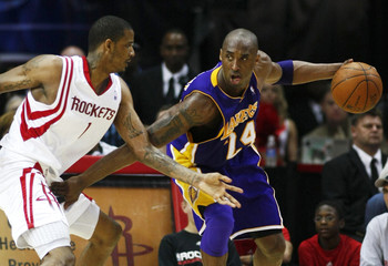 Los Angeles Lakers guard Kobe Bryant keeps the ball away from Houston Rockets guard Trevor Ariza during the second half of their NBA basketball game in Houston.