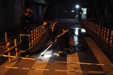 Firefighters wash bloodstains off a street after a rampage by a knife-wielding man outside a primary school in Shanghai