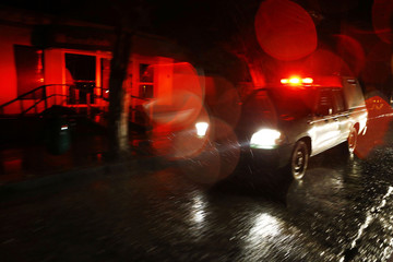 A police vehicle patrols a commercial area during a blackout after an earthquake hit Chile's central zone, in Santiago