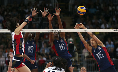 South Korea's Kim Yeon-koung spikes the ball against Destinee Hooker, Foluke Akinradewo and Logan Tom of the U.S. during their women's Group B volleyball match at the London 2012 Olympic Games at Earls Court in London