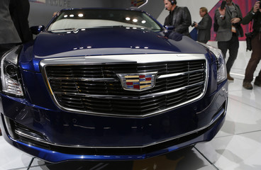 Members of the media examine the Cadillac ATS Coupe as it is unveiled during the press preview day of the North American International Auto Show in Detroit