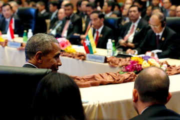 Obama confers with members of his delegation after remarks to a US-ASEAN meeting at the ASEAN Summit in Kuala Lumpur