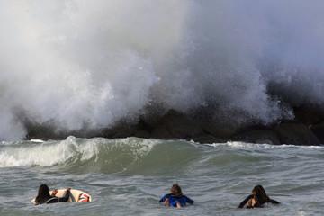 Surfers float in Mediterranean as a wave breaks on rocks off the coast of Ashkelon