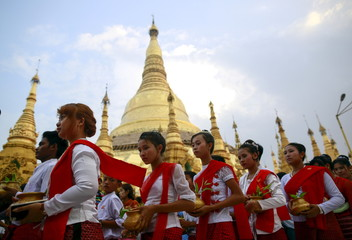Devotees carry water pots to water a Bodhi tree during Kason Watering Festival celebrations at the Shwedagon Pagoda in Yangon