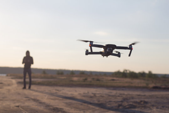 Close up picture of black flaying quadrocopter dron and pilot siluette in sunset light background, tourist use dron helicopter to photography or filming desert landscapes
