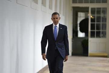 U.S. President Obama walks colonnade from residence of White House to the Oval Office in the West Wing, in Washington