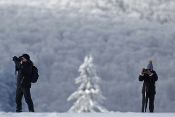 Hikers wear snow shoes as they make pictures on a cold and sunny winter's day at the Champ du Feu near Strasbourg