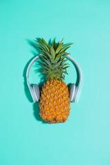 Fashion pineapple with headphones listens to music over blue background