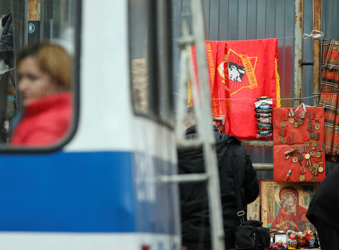 A woman sits in a trolleybus as a flag of the former Young Pioneer Organisation of USSR with a portrait of Lenin, icons and old soviet medals are on sale on the street in central Chisinau
