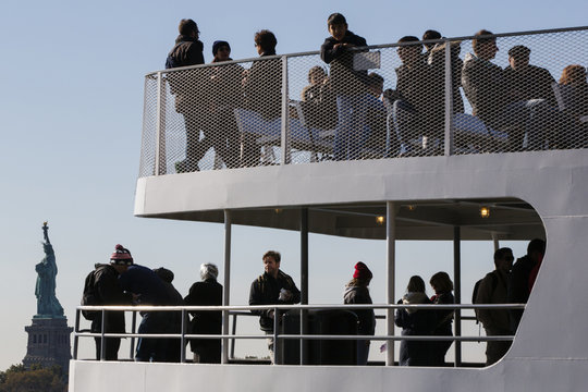 Tourists stand on deck of a boat as it motors past the Statue of Liberty National Park in New York